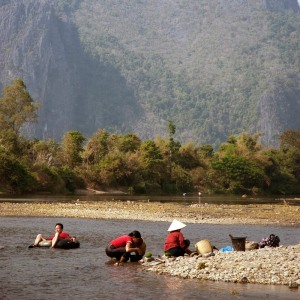 man tubing, women working, vang vieng, laos