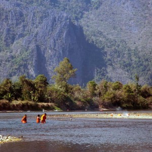 buddhist monks wading through river, vang vieng, laos