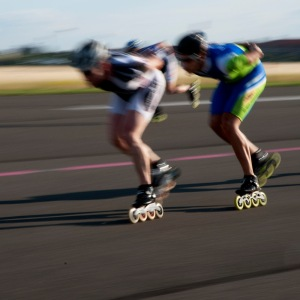 rollerbladers nearing liftoff speed on the airstrip