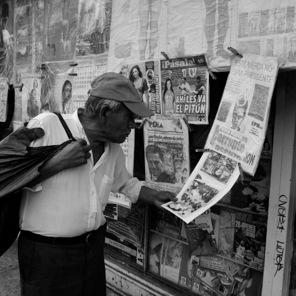 Man reading the daily paper outside a newsstand, whose owner clearly does not sympathize witht he new president-elect.