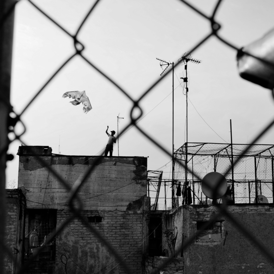 This is one of my all-time favorite photographs. This kid on the rooftop tried desperately to get his kite to lift off for hours. Without much success. My worry was he'd tumble off the edge onto the pavement, many, many meters down.