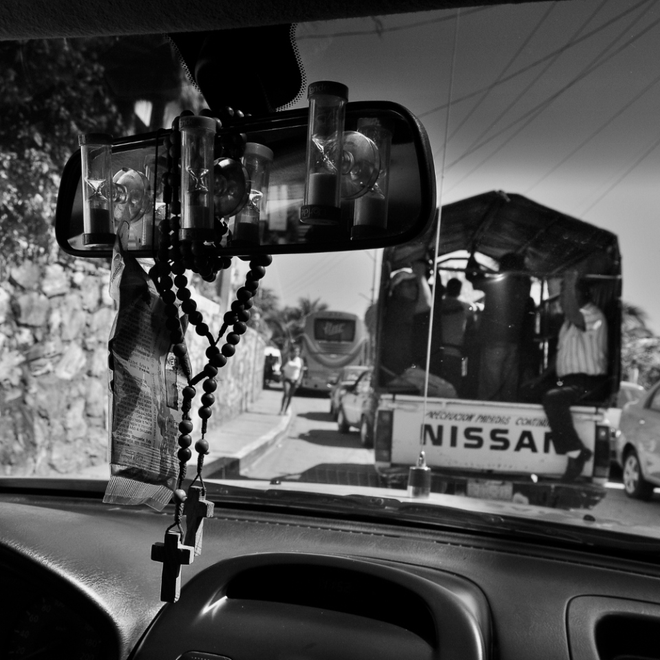 "And when it's time to leave Mazunte, you can take a ""colectivo"" (shared) taxi. If you're lucky, you get to ride shotgun. The other choice is to hop onto the back of a pickup truck, as the one visible through the windshield. The rearview mirror? It's just ideal for a few hourglasses and a rosary or two. I mean, who really needs a rear view anyway...?"