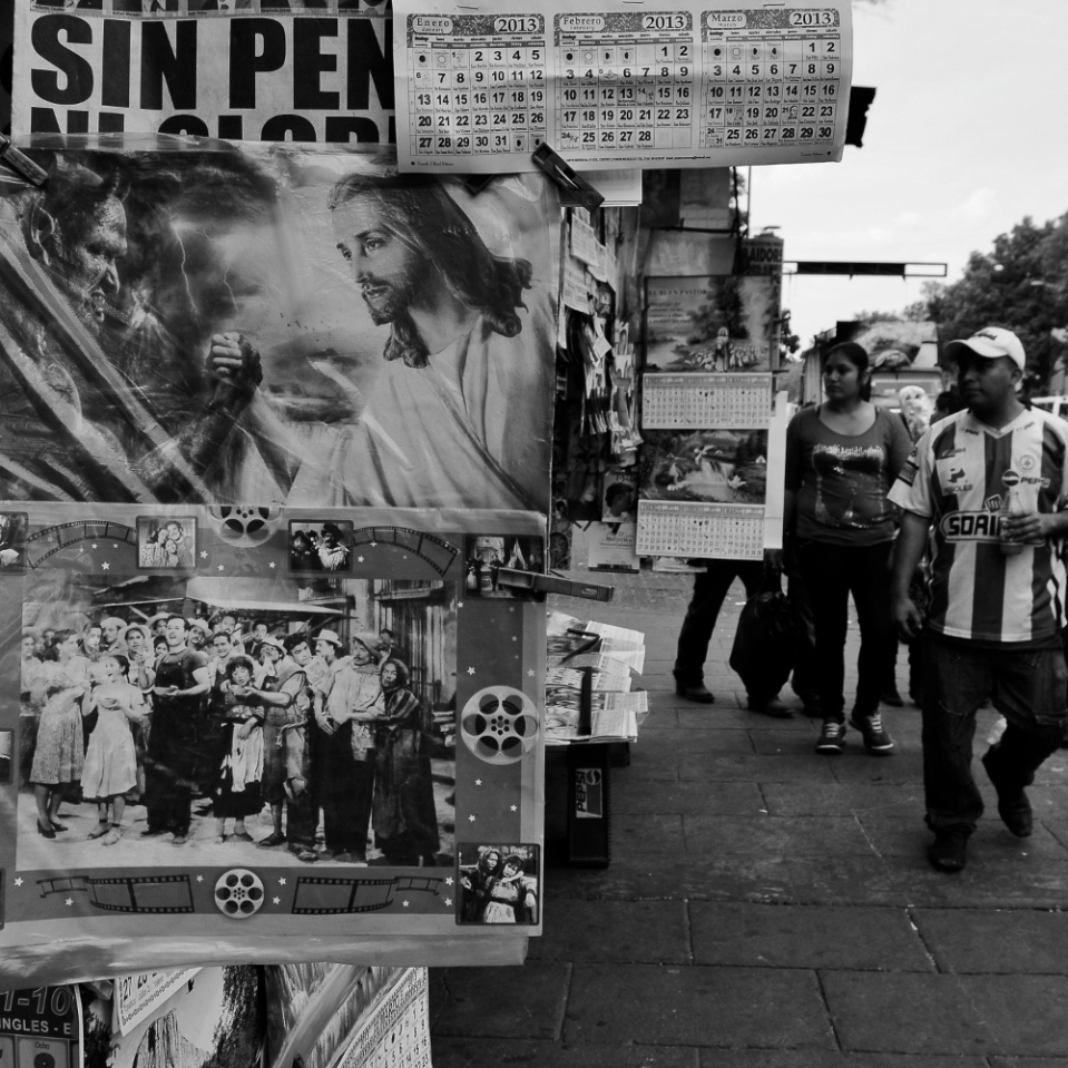 Two things Mexicans are absolute fans of is fooball (soccer) and almost anything religious. In this picture a man wearing a sports t-shirt walks past a newsstand selling a poster of Jesus armwrestling with the devil.