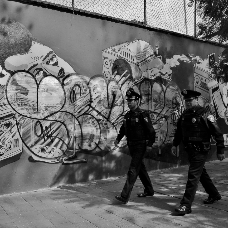 A mural painting defaced by some graffiti serves as the backdrop to these Mexico City cops apparently trying hard to look like New York City's. (yes, i did ask permission for this shot: cops anywhere can be potentially touchy subject.)