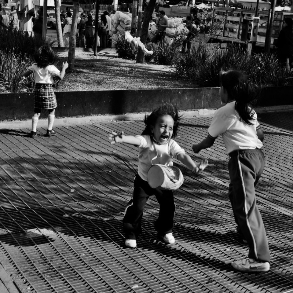 In Plaza de san Miguel Arcangel is a large ventilation grid for the underlying metro, Mexico City's efficient subway network. The updraft is so powerful that these little girls were trying hard to fall over, but the air flow kept them on their feet.