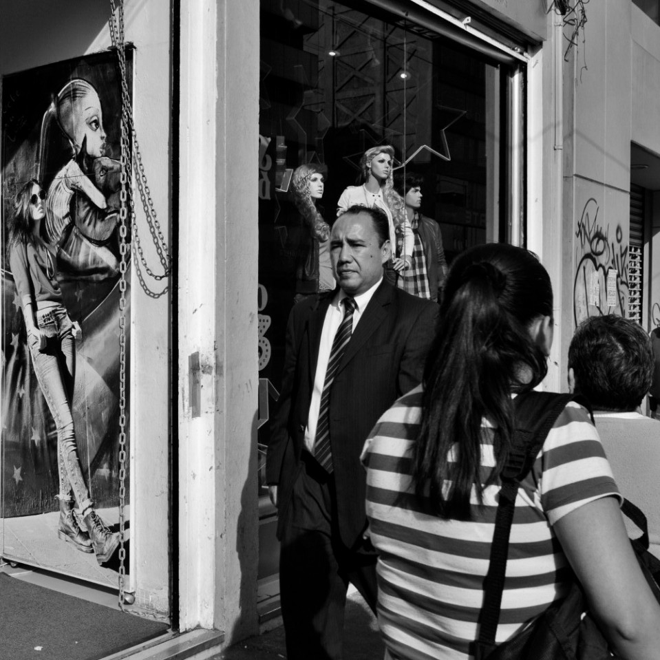People busy going to and fro while a model chills out leaning on a mural in the large shop window photograph.