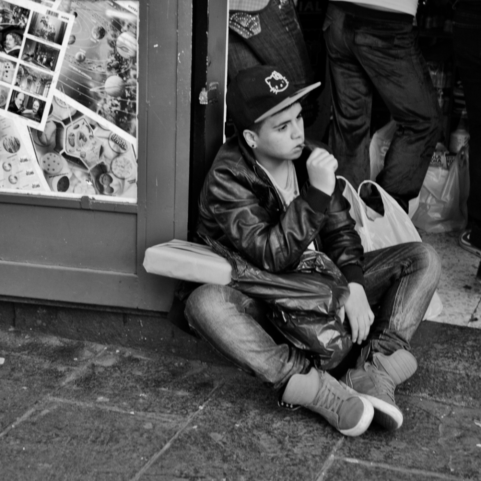 ...while this other young man sitting on a  doorway seems absolutely bored out of his mind as his mother was doing the shopping.