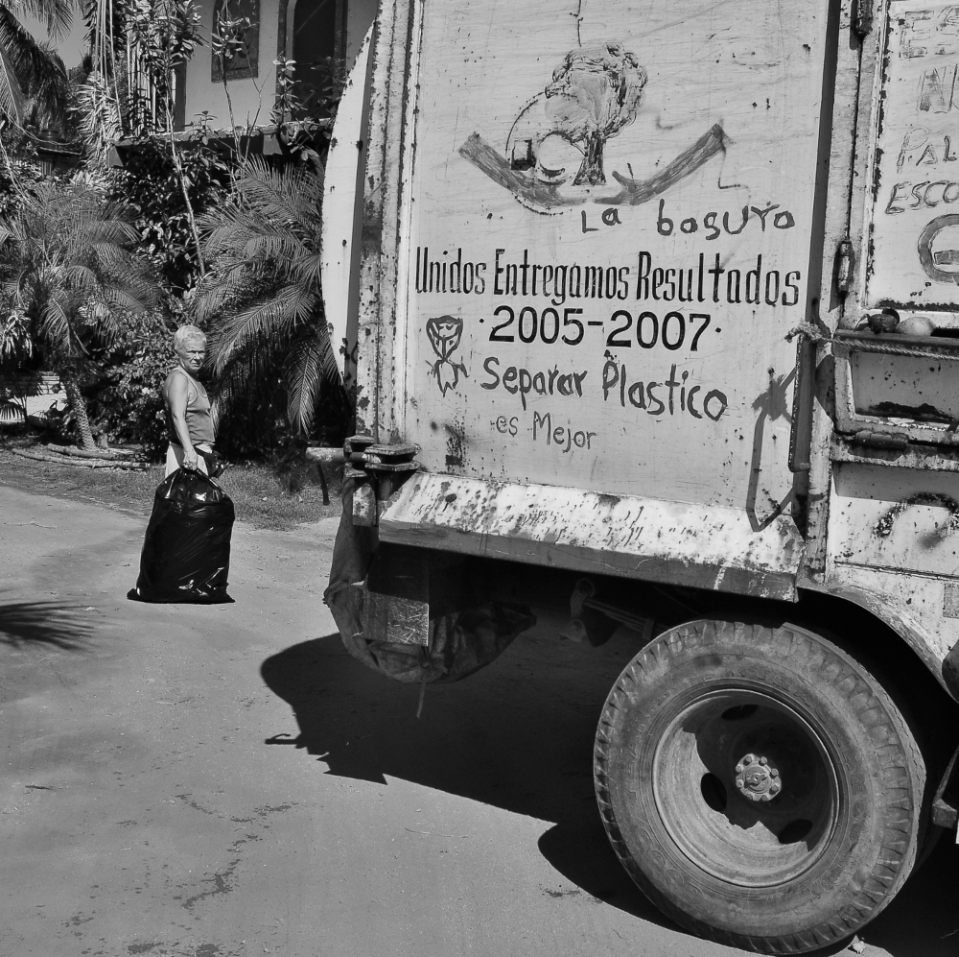 "Trash truck with handwritten note ""it is better to separate plastic""."