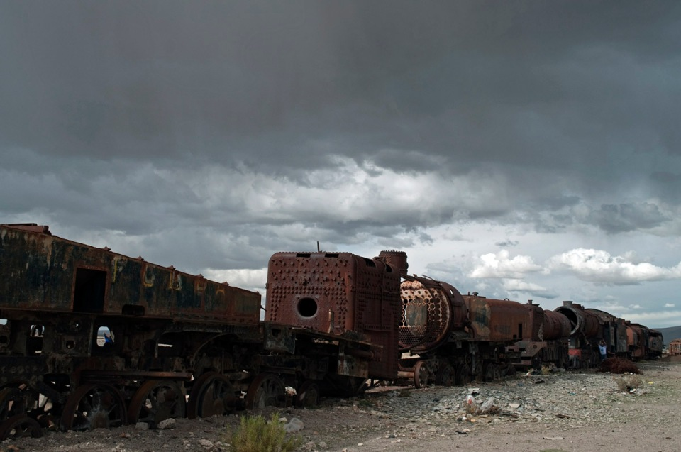 Abandoned steam locomotives under a gloomy sky at Uyuni train cemetery, Bolivia