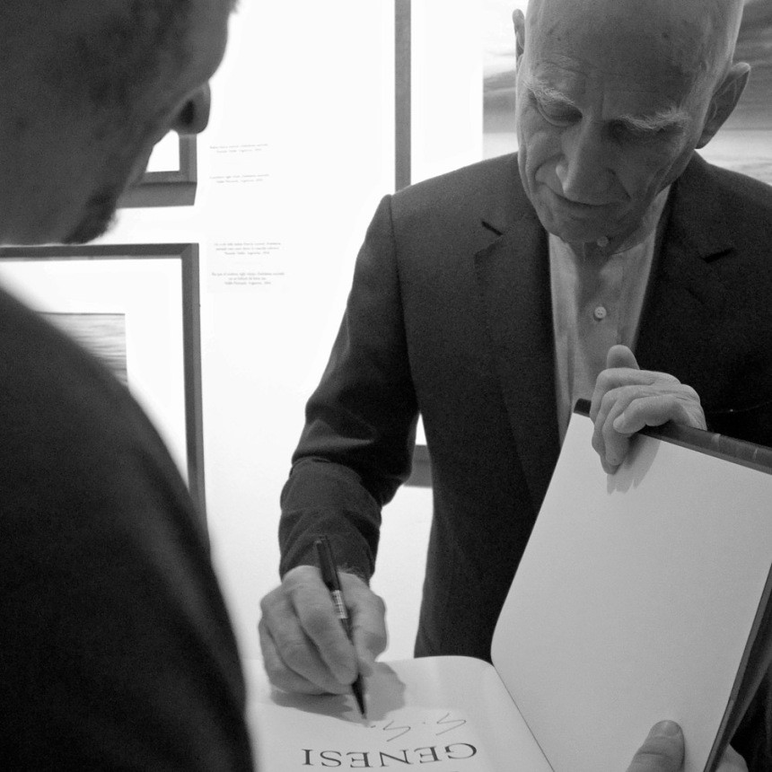 Sebastiao Salgado, as he signs a fan's copy of his rewrite of the Genesis.