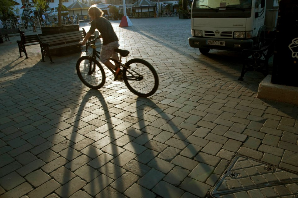 Child chases the final rays of sun in Casemates Square.