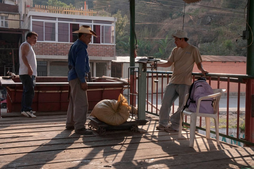 An individual coffee picker brings his daily sack of beans to the local mill, where it is weighed and payed cash.