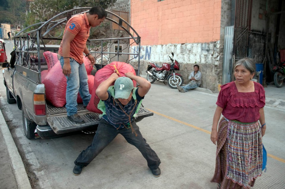 "The lady on the right is a ""buyer"" who purchases coffee beans from the pickers in the mountains, drives them to the mill in her pickup truck, and resells it for a premium."