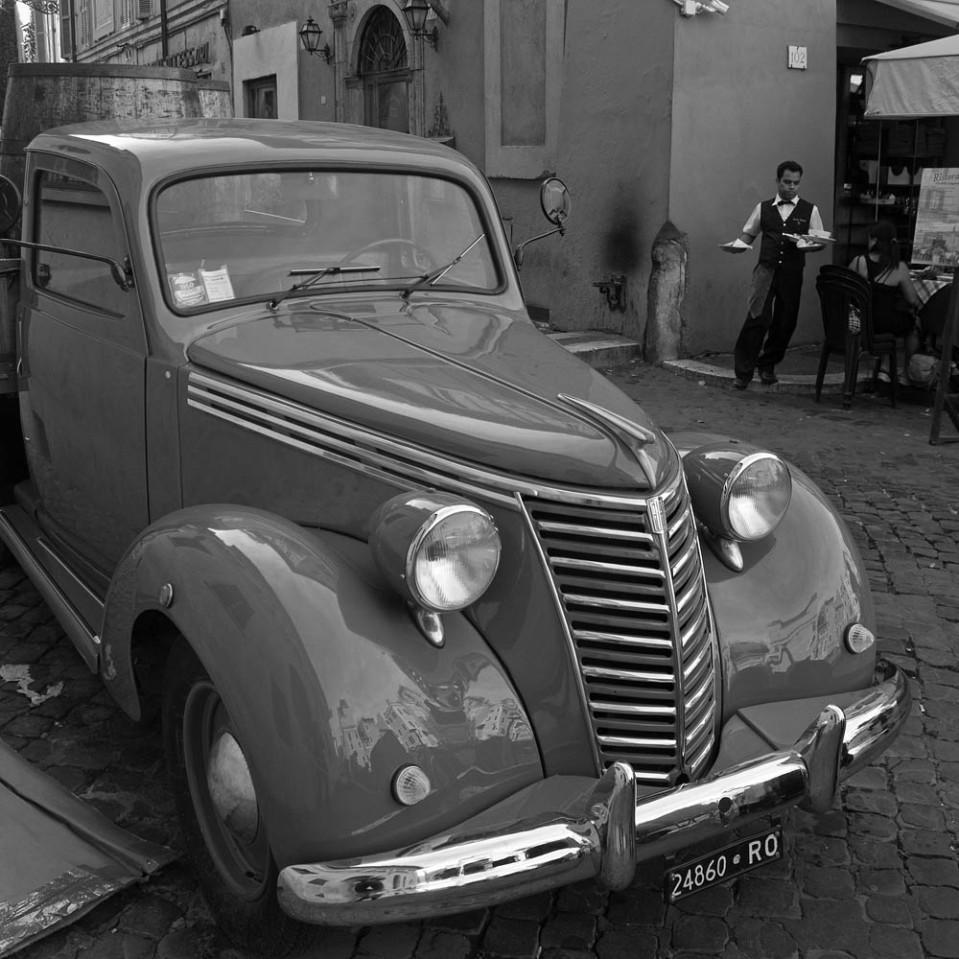 Vintage Fiat pickup truck parked on Via della Lungaretta near Carlo Menta restaurant. In the background, a wiater carries dishes of traditional Roman fare.