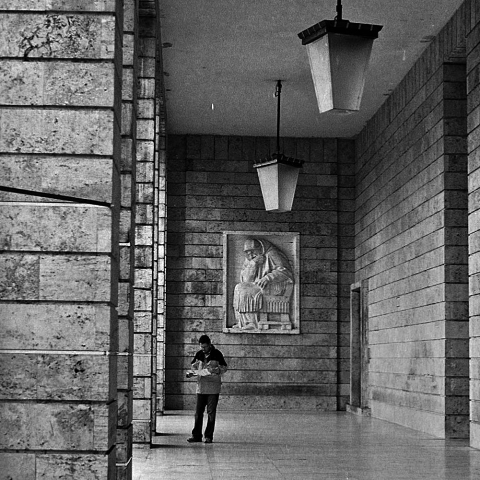 Man checks map in the colonnade at Largo Augusto Imperatore, while a bas-relief appears to read over his shoulder.