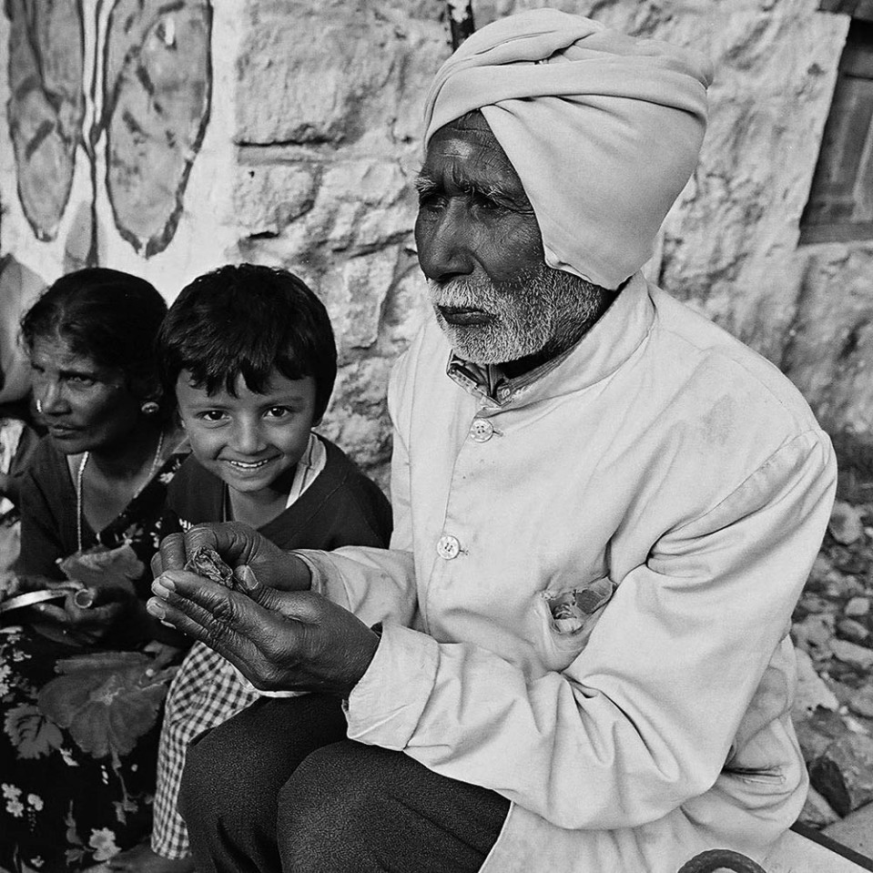 In the mountains, at Kodaikanal, an elderly gentleman rolls up a bit of betel nut for a chew.