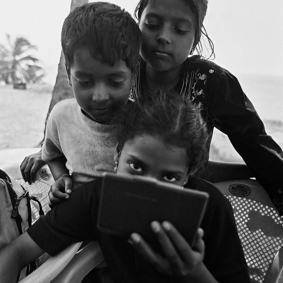 Three young Indians looking into an electronic device, Varkala.
