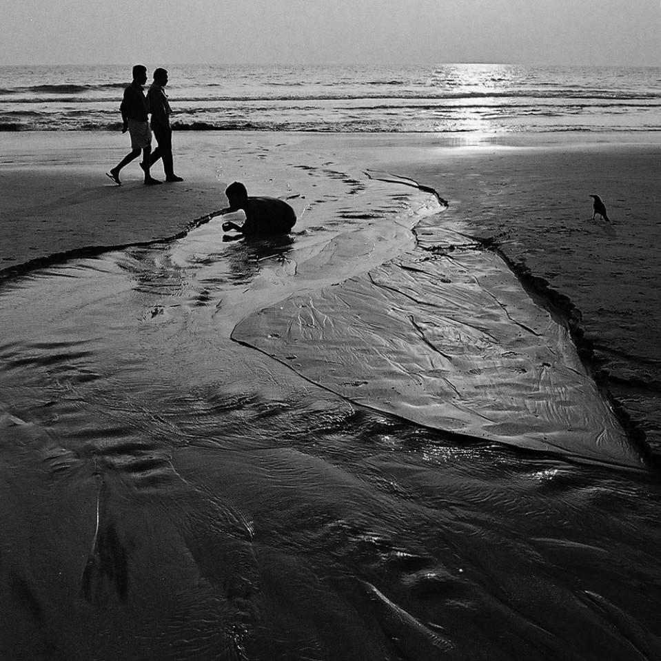Peace at sunset: a crow, a creek, a beach, a buddy. Varkala, Kerala.