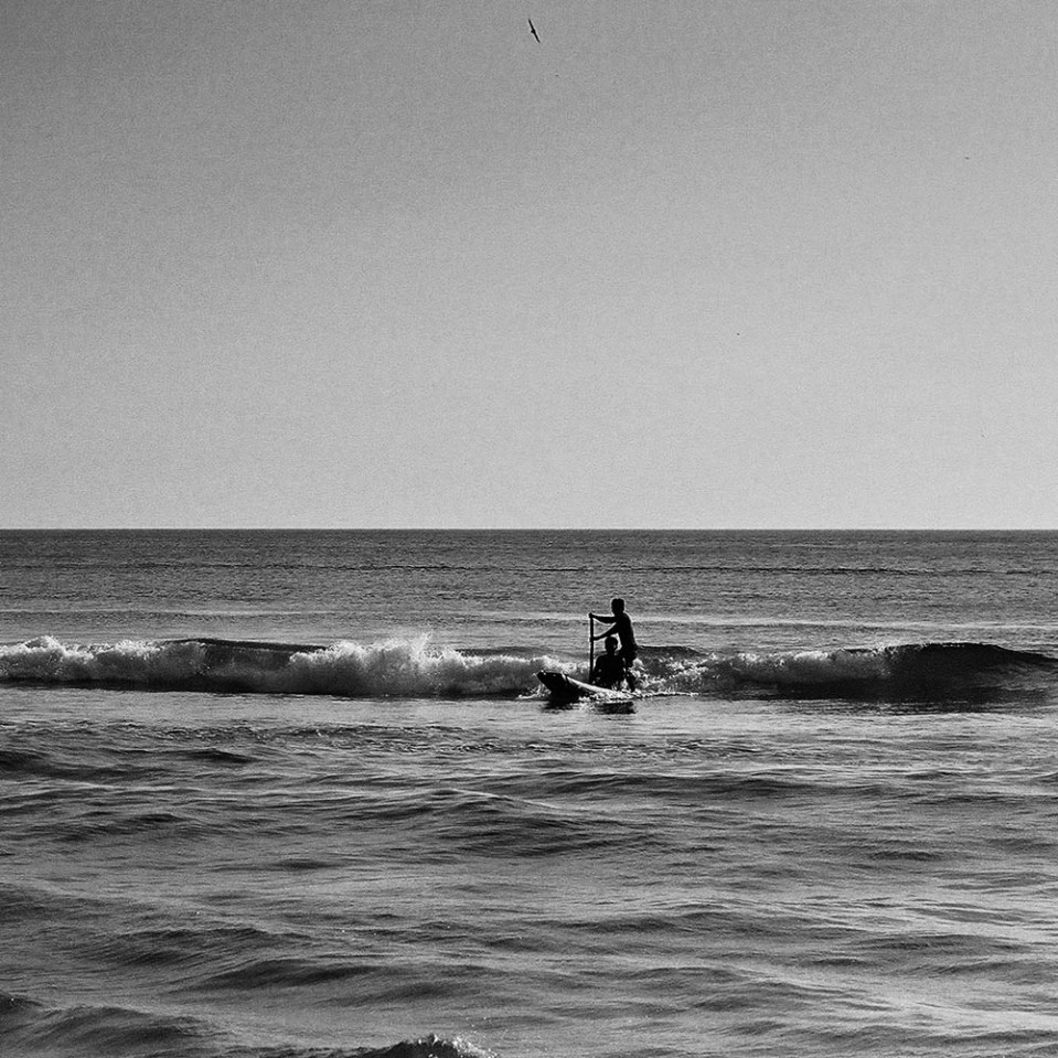 Surf's up! Locals catching a wave on a small log canoe at Varkala, india, 2003