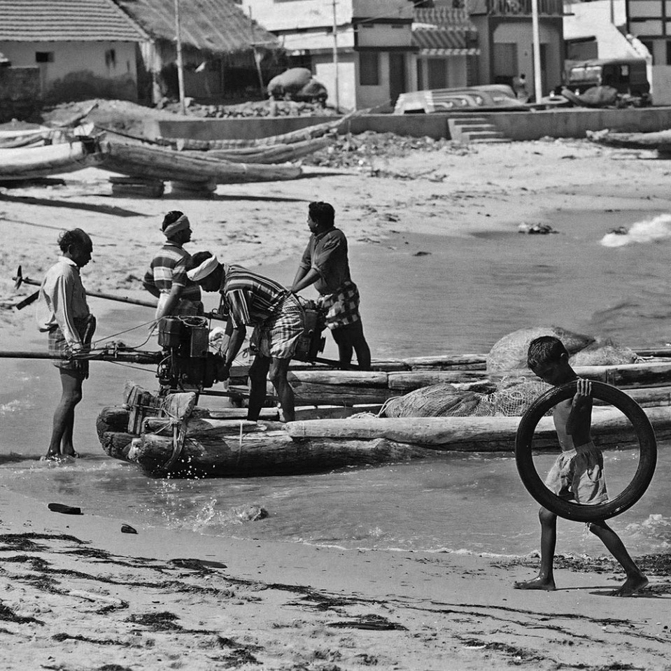 Of course, there's also the age old art of chasing and fetching an old tyre. The fishermen in the bacgkround prepare the log boats for the evening's outing.