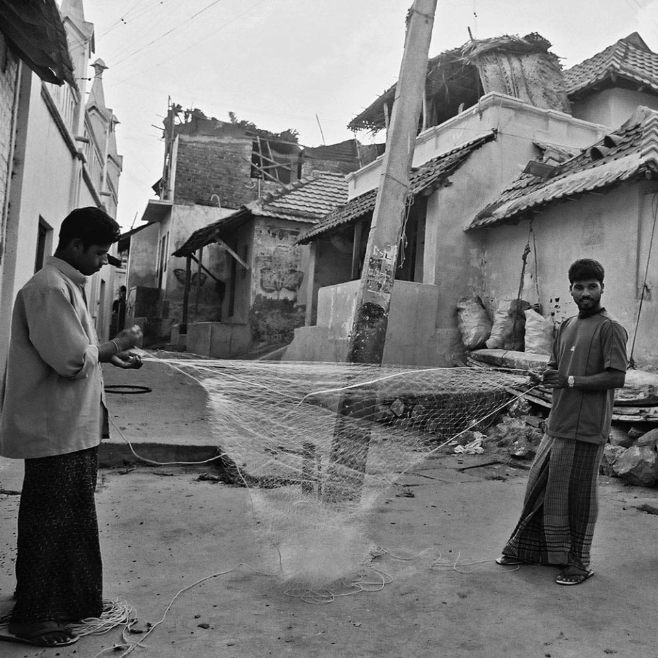 In the narrow alleys, some men clean and mend the fishing nets.