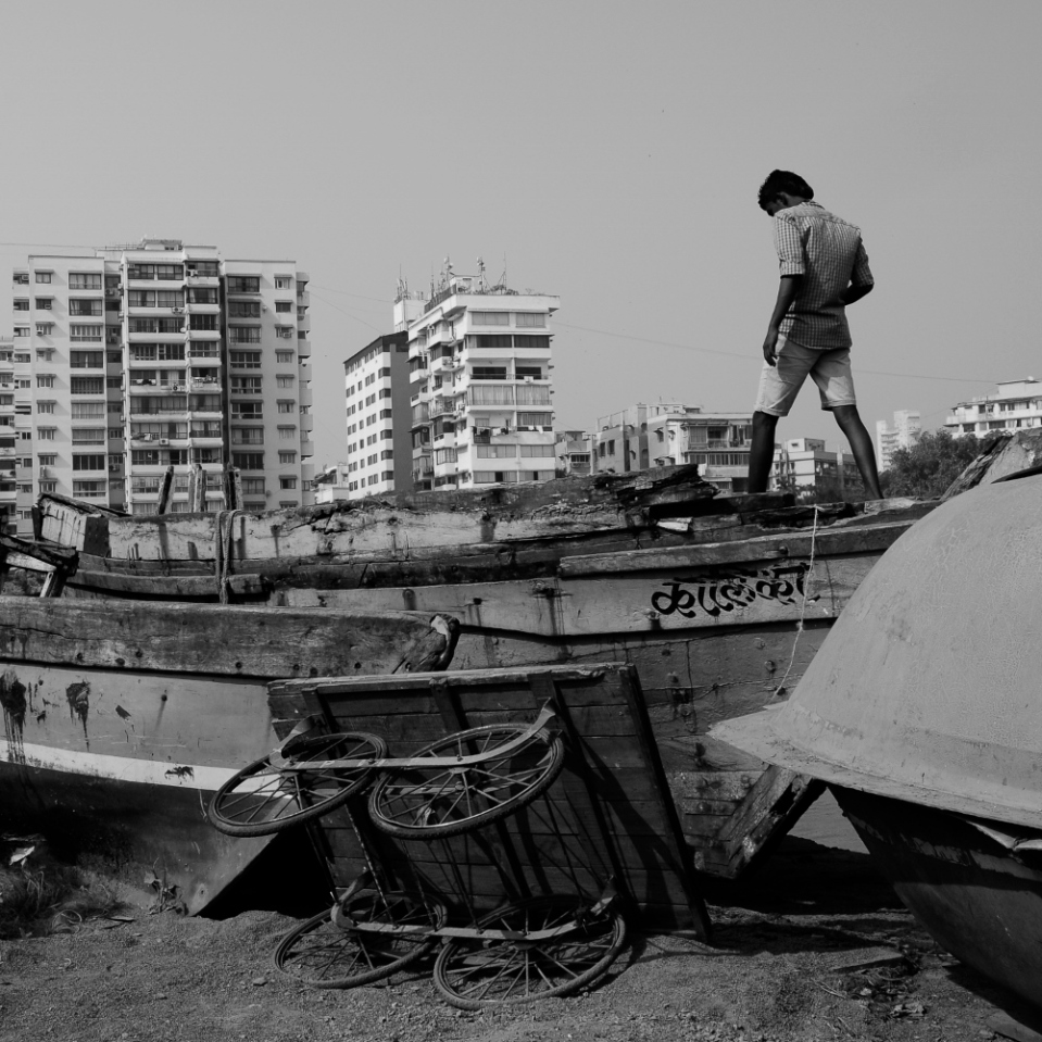 "In this ""fishing village"" boats of all sorts line the sides of the streets, not far from modern, concrete high-rise buildings. And it's all justa a stone's throw from Bombay's most celebrated monument."