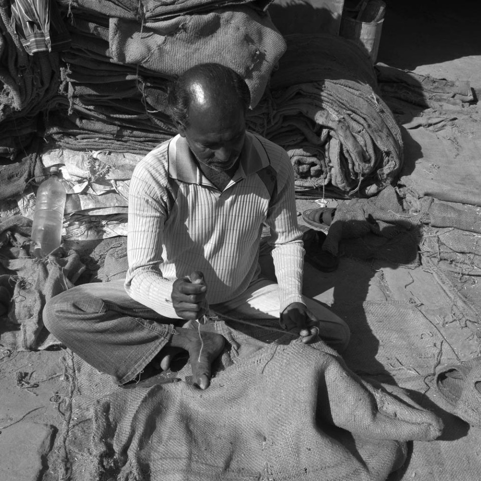 This man was busy mending sacks with needle and thread.