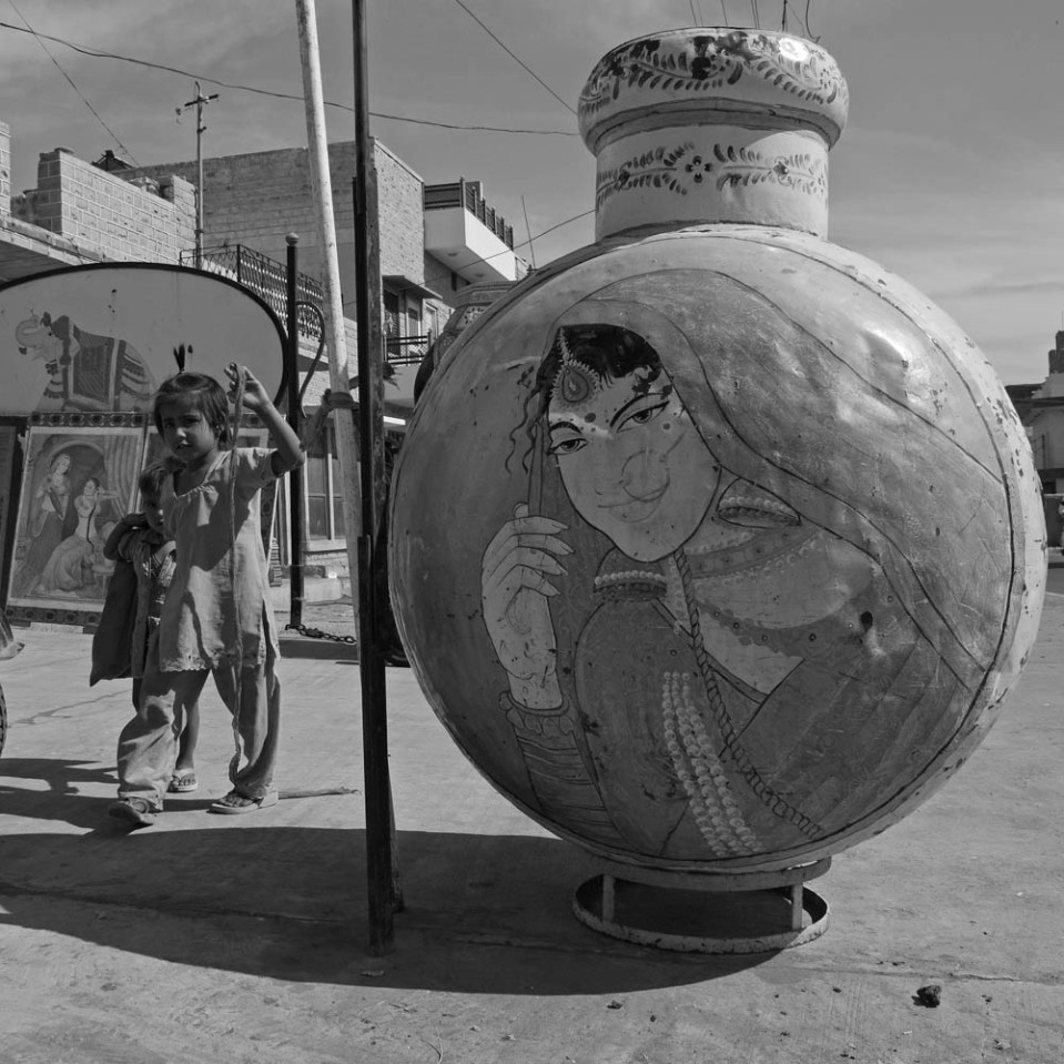 There are little girls going home after school and there are oversized jugs bearing portraits, somewhere along the road that leads to the hilltop fort.
