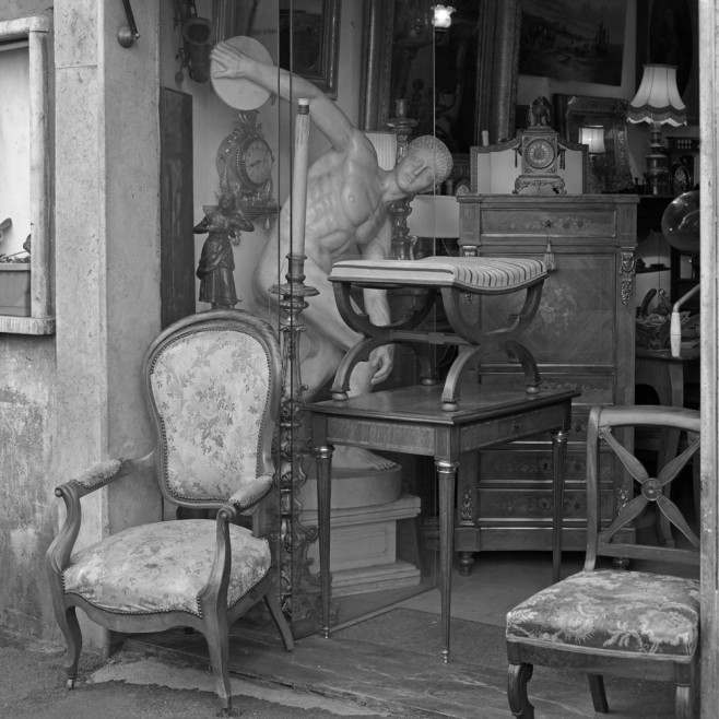 Antique shop. The statue represents a Stones fan about to process a Betles record...