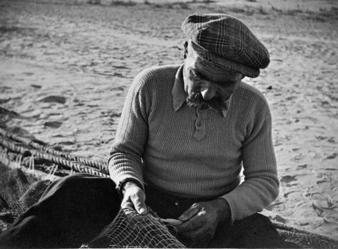 Mending net. The moustache hints that this may be the same gentleman as the one in the photo with the child.